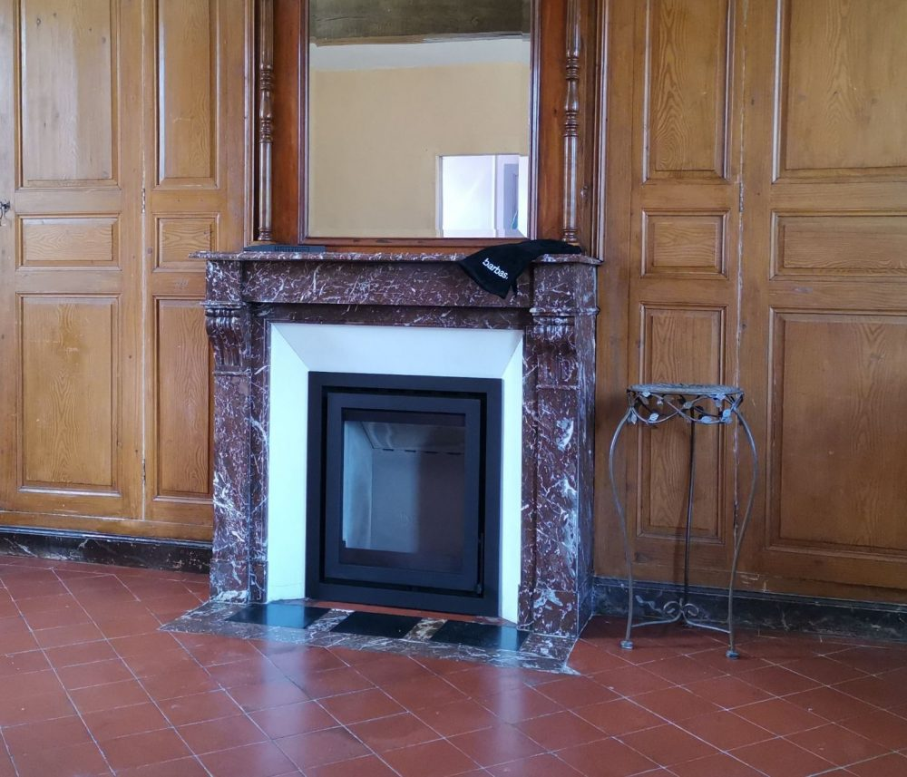 Insert à bois dans cheminée en marbre